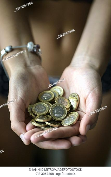 Hands full with UK Pound Coins