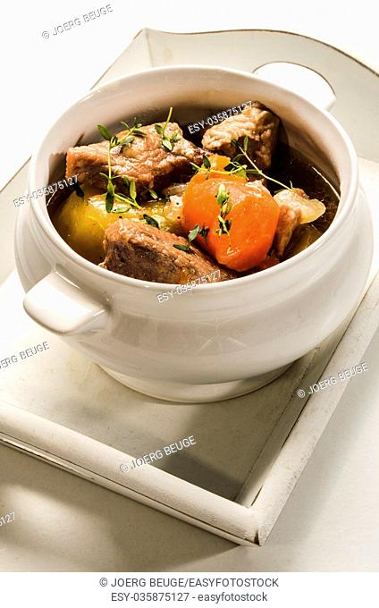 traditonal irish stew with thyme in a bowl, served on a tray