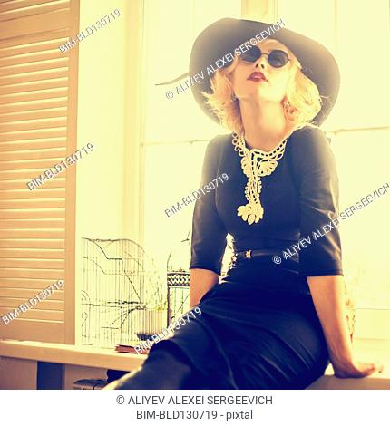 Caucasian woman wearing sunglasses and hat indoors
