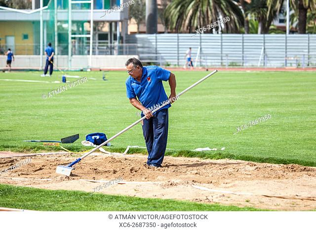 male worker raking the sand pit after a Long jump competition