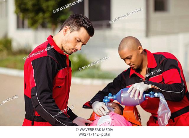 Paramedic giving oxygen to injured girl