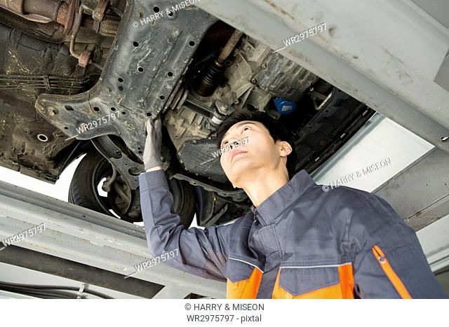 Young mechanic repairing a car looking up