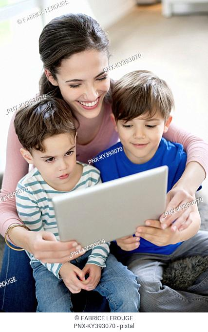 Woman showing a digital tablet to their children