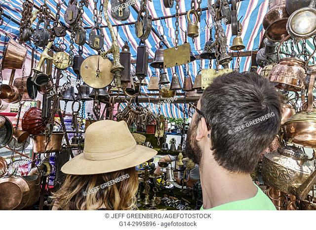 Argentina, Buenos Aires, San Telmo Plaza Dorrego, art fair, antiques, marketplace vendors vendor booths stalls, shopping, bells, copper, man, woman, couple