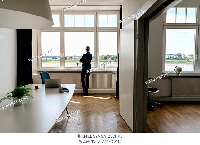 Businesswoman standing in modern office looking out of window