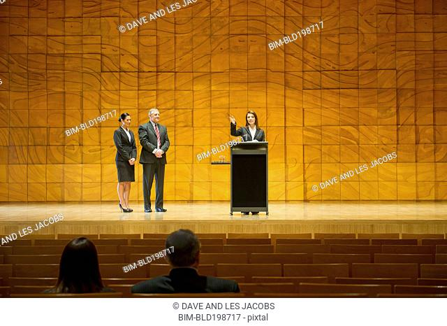 Business people on stage making speeches