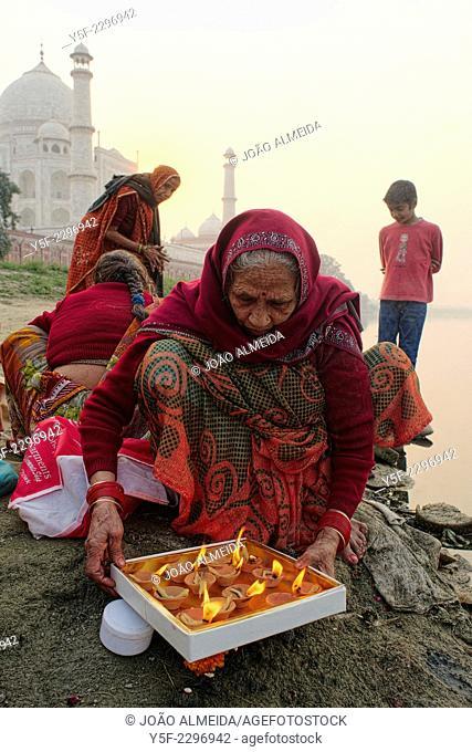 Families preparing offering in the Yamuna river behind the Taj Mahal