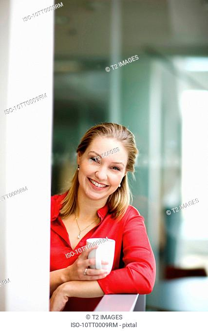 Woman holding a cup, smiling