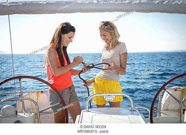 Croatia, Adriatic Sea, Young women on sailboat learn how to tie knots