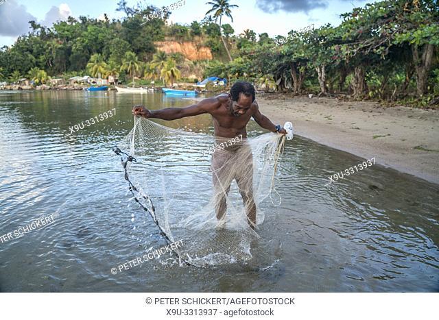 Fischer mit seinem Netz am Strand von Calibishie, Parish Saint Andrew, Dominica, Karibik, Mittelamerika | fisherman with his net at the beach in Calibishie