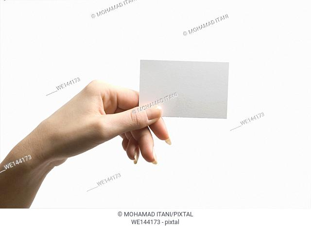 Hand holding a blank business card against a white background