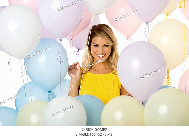 Caucasian woman standing with balloons