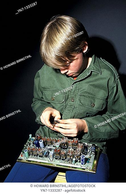 young boy working on a circuit board on his lap