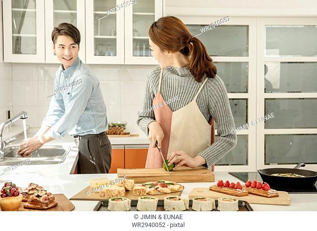 Young smiling couple preparing food for party