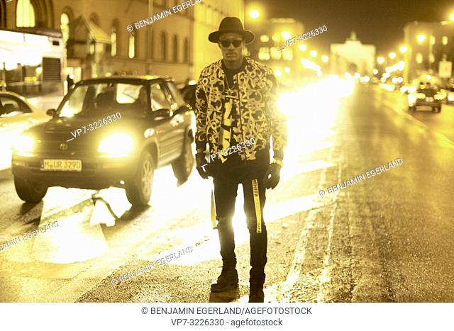 fancy blogger man standing at city street at night, wearing stylish outfit, car lights, traffic, cool attitude, at Ludwigstraße in Munich, Germany