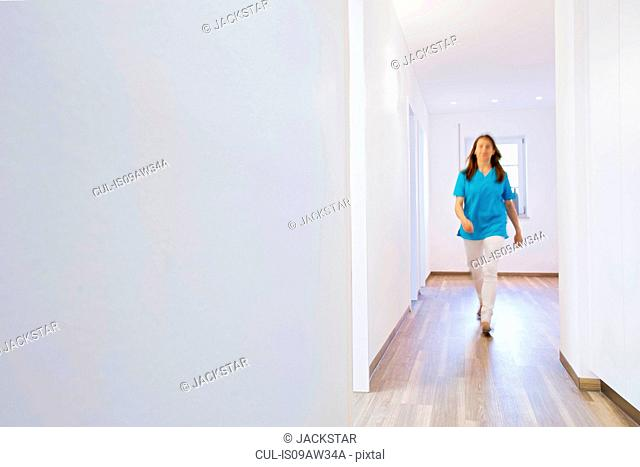 Full length front view of nurse walking in clinic corridor