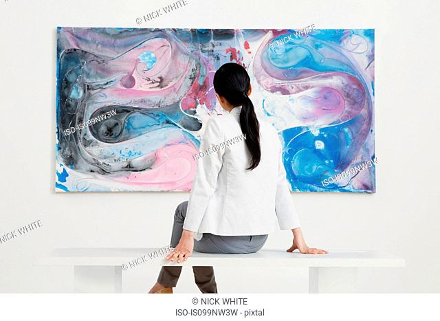 Young woman looking at oil painting in gallery