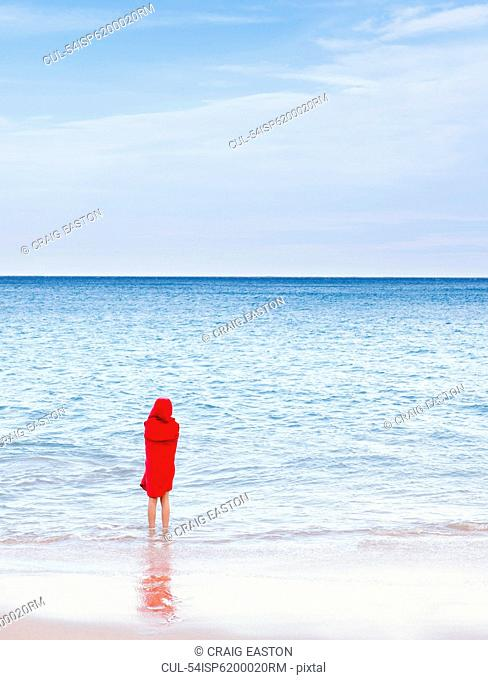 Girl standing in waves on beach