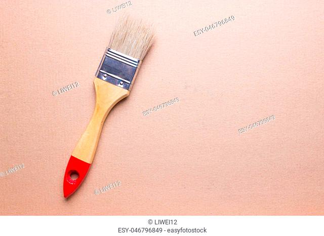 Closeup of one paint brush on wooden table with space for text