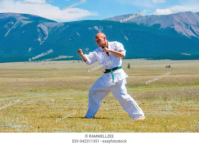 Man in white kimono and black belt training karate on mountain background. Altay, Russia