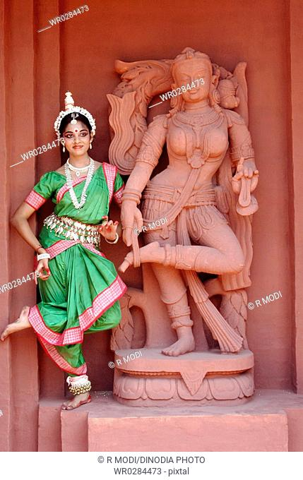 Woman performing classical traditional Odissi dance at statue on stage MR736D