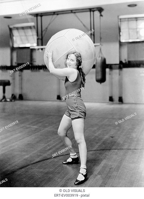 Woman in gymnasium with huge ball All persons depicted are not longer living and no estate exists Supplier warranties that there will be no model release issues