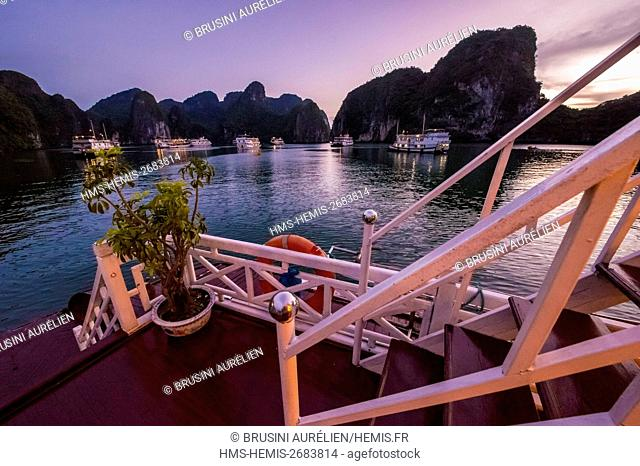 Vietnam, Gulf of Tonkin, Quang Ninh province, Ha Long Bay (Vinh Ha Long) listed as World Heritage by UNESCO (1994), at anchor in a cove at sunset aboard a...