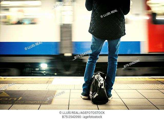 Back view of a man unrecognizable, with a bag between his legs, waiting for a train on the platform of an Underground station