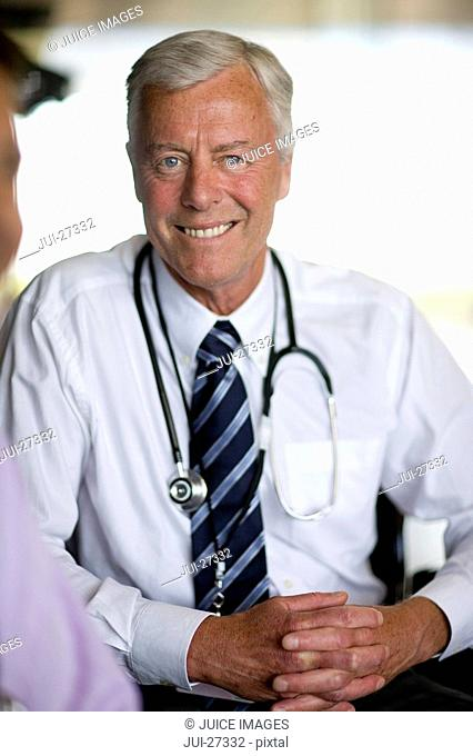 Smiling doctor with stethoscope with hands clasped