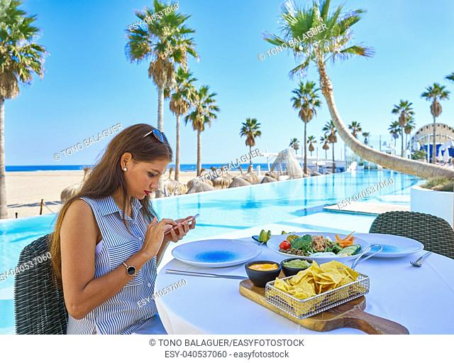 Young woman texting with smartphone chat on a swimming pool restaurant
