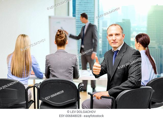 business, teamwork, people and success concept - confident businessman with team in office showing thumbs up
