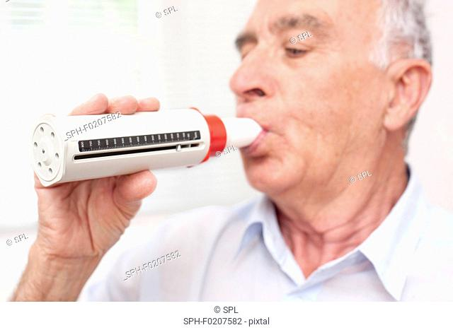 Man exhaling into a peakflow reader