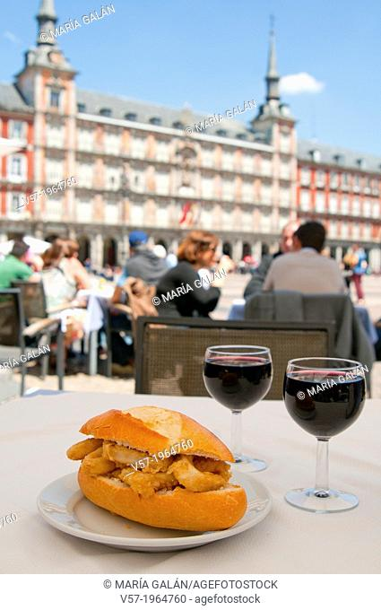 Fried squids sandwich with two glasses of red wine in a terrace. Main Square, Madrid, Spain