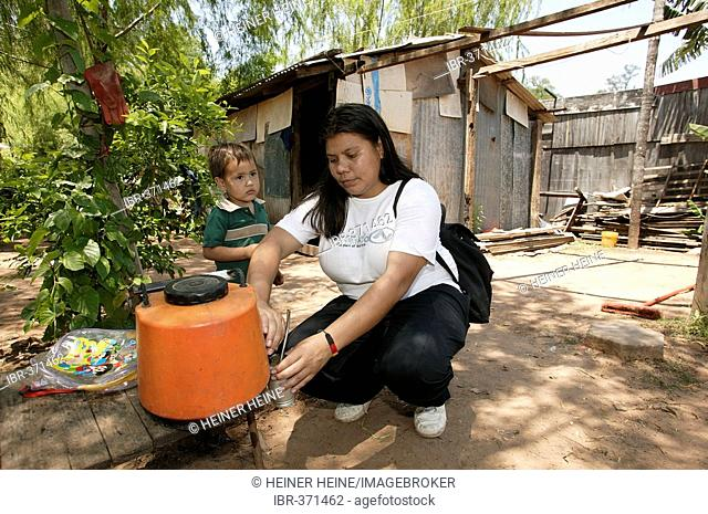 Guarani pouring Mate tea cooking in front of her hut, in the poor area of Chacarita, Asuncion, Paraguay, South America