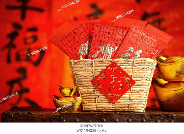 Close-up of gold ingots and red envelopes