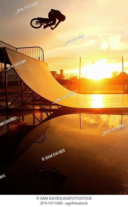 BMXer riding a halfpipe in Swansea, South Wales during a sunset, rider silhouetted with his reflection in a puddle