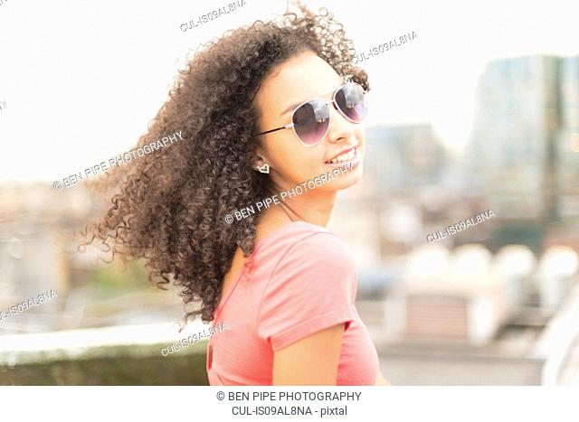 Young woman wearing sunglasses looking over shoulder
