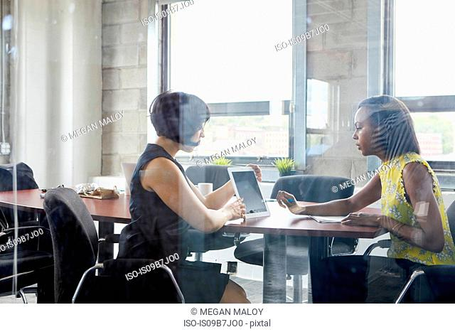 Two women working together in meeting room, brainstorming, using digital tablet