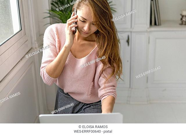 Young businesswoman, using laptop, talking on the phone