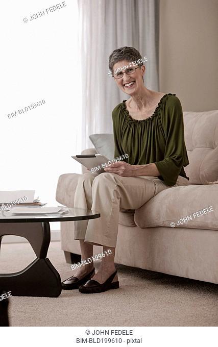 Caucasian woman using digital tablet on sofa