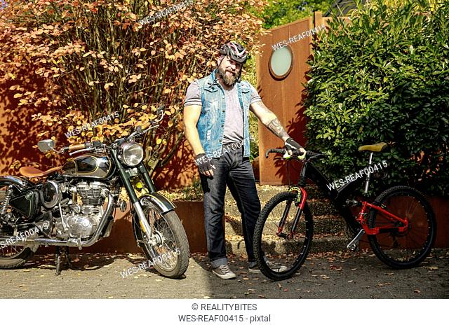 Portrait of man switching from motorbike to bicycle