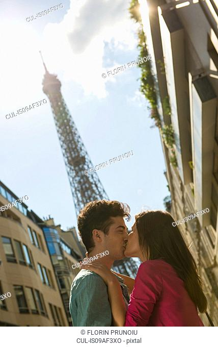 Young couple sharing a kiss in front of Eiffel Tower, Paris, France