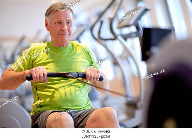 Senior man exercising on rowing machine in gym