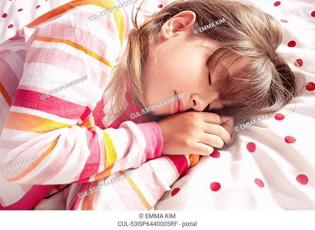 Girl sleeping on polka dot blanket