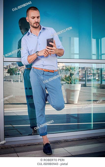 Businessman leaning against office exterior texting on smartphone, Cagliari, Sardinia, Italy