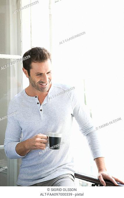 Man standing by window with mug in hand