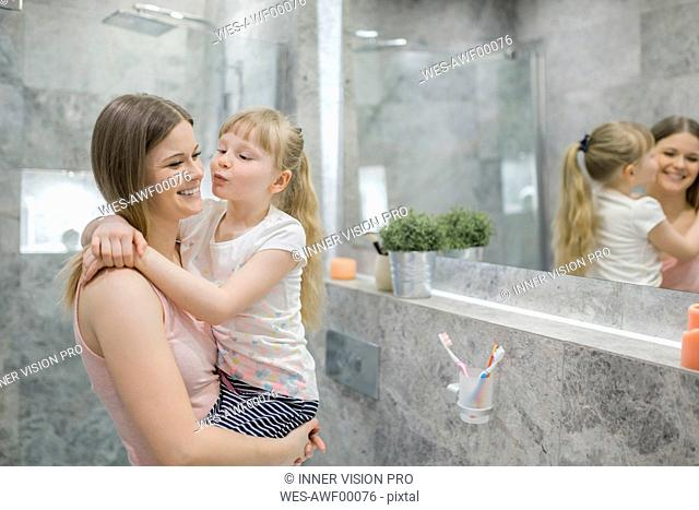 Little girl embracing her mommy in bathroom