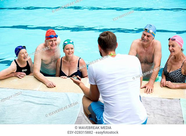 Male instructor assisting senior swimmers at poolside