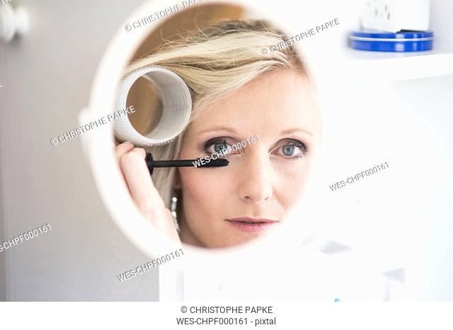 Mirror image of blond woman with curler applying mascara