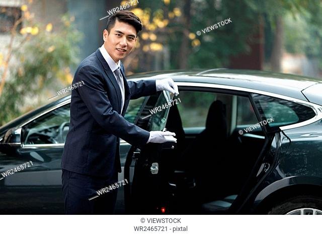 Young man standing by car